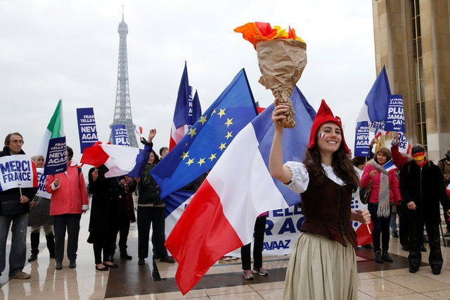 People gather with French and European flags near the Eiffel Tower and hold placards with the message,