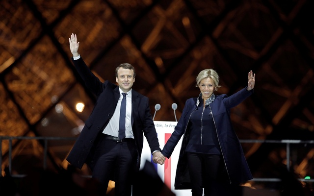 French President elect Emmanuel Macron and his wife Brigitte Trogneux celebrate on the stage at his victory rally near the Louvre in Paris, France May 7, 2017. Reuters