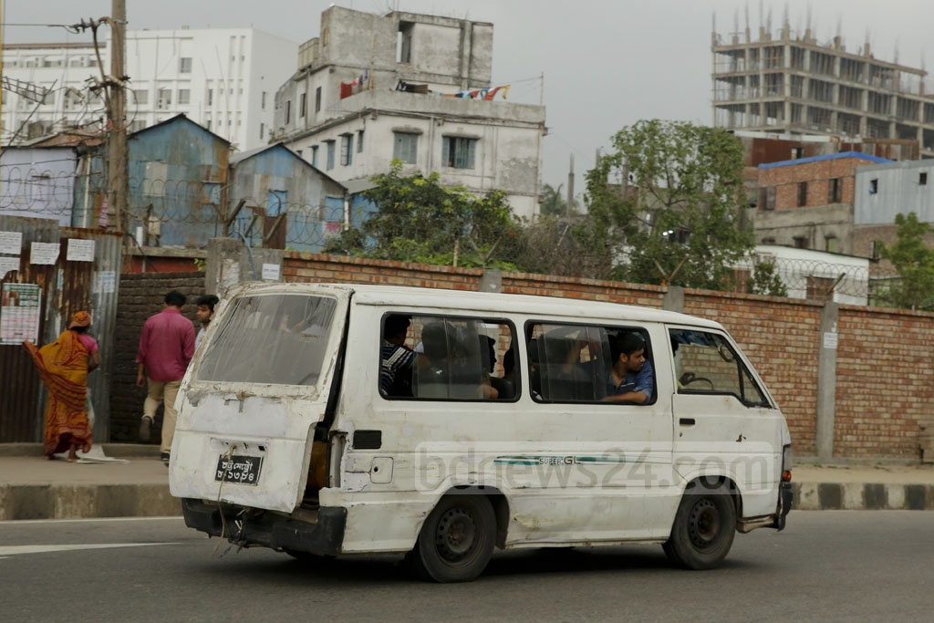 The rickety, unfit micro-bus is clearly an eyesore in the pleasent surroundings of Hatirjheel in Dhaka. Visitors board in the risky vehicles to take a tour of the area due to shortage of public transport in the area. Photo: mostafigur rahman