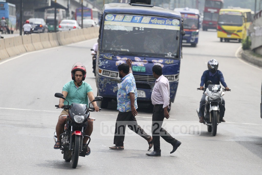 Pedestrians captured when breaking the law by crossing the busy street at Dhaka's Kuril on Tuesday. Photo: abdul mannan
