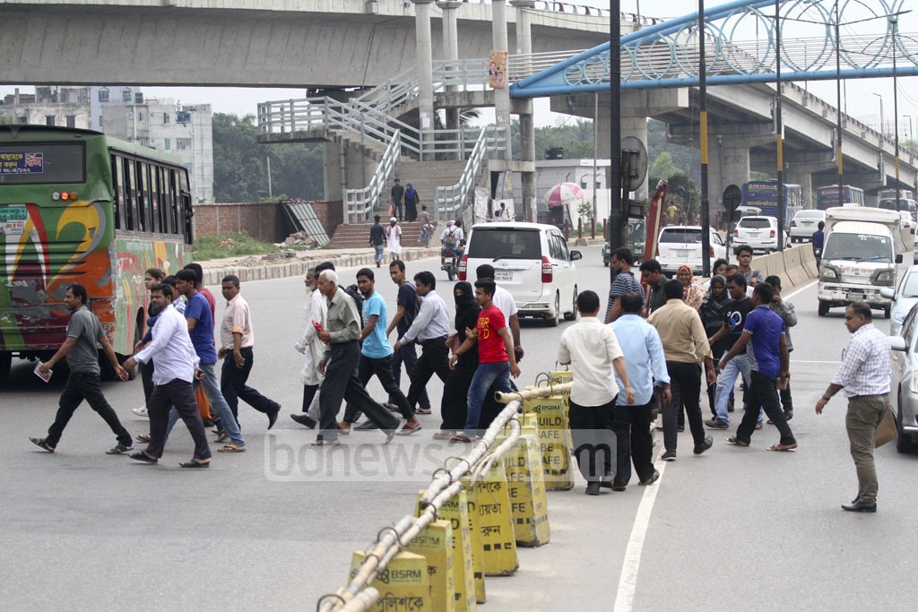 Pedestrians cross the busy street on foot leaving the footover bridge just behind. The photo was taken from Dhaka's Kuril Rail Crossing area on Tuesday. Photo: abdul mannan