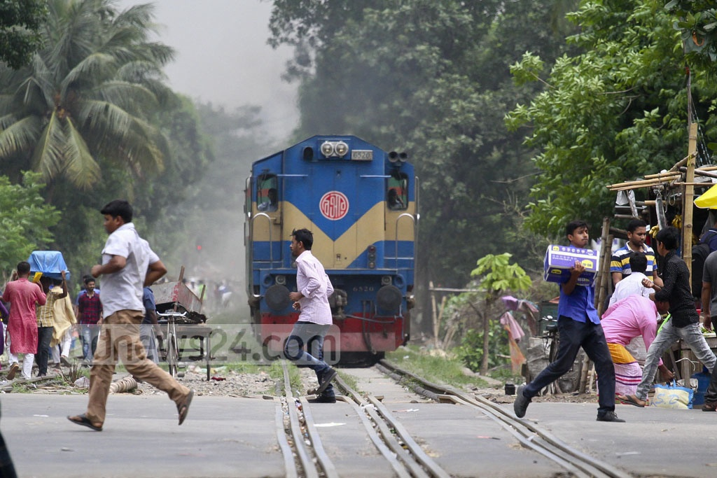 In sheer disrespect to traffic rule, pedestrians take the risk of crossing the Mohakhali level crossing in Dhaka when a train is too close to crush them. The photo was taken on Tuesday. Photo: abdul mannan