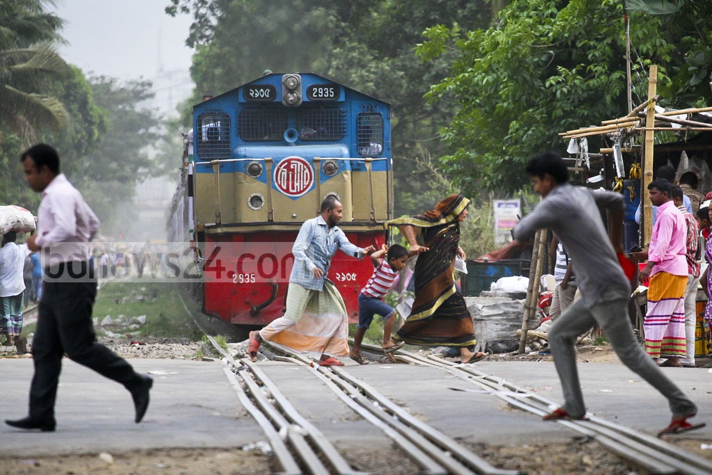 The family was about to be crushed when they ran through the Mohakhali level crossing in Dhaka as the train was only at arm's length. The photo was taken on Tuesday. Photo: abdul mannan