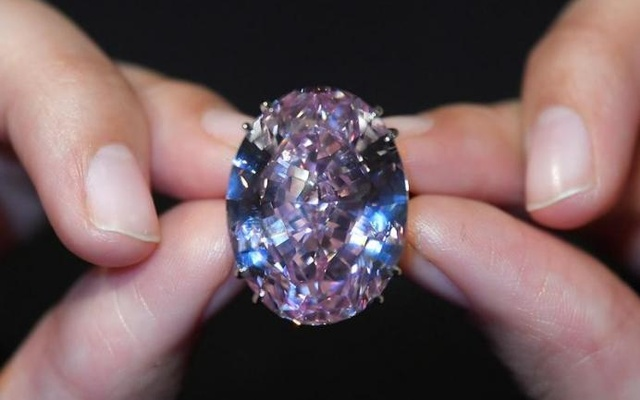 A model poses with a 59.60-carat mixed cut diamond known as 'The Pink Star', the largest Internally Flawless Fancy Vivid Pink diamond ever graded by the Geological Institute of America (GIA), ahead of being auctioned in Hong Kong next month by Sotheby's which said it could fetch upwards of $60 million (GBP £48.4 million) to make it the most expensive diamond of its kind ever sold, in London, Britain, March 20, 2017. Reuters
