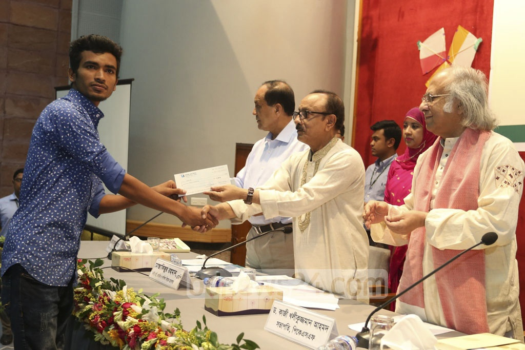 Primary and Mass Education Minister Mostafizur Rahman hands out scholarships to Palli Karma-Sahayak Foundation students on Thursday.