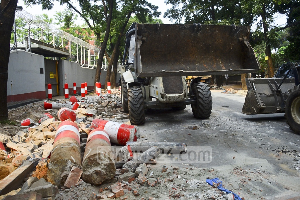 The DNCC bulldozer removing the heavy iron pillars implanted encroaching the pavement around Australian High Commission located at the Gulshan North Avenue in the capital on Friday.