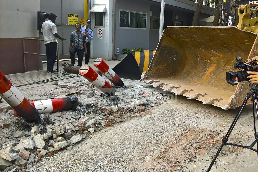 The DNCC bulldozer swings into action to remove the heavy iron pillars implanted encroaching the pavement around Australian High Commission located at the Gulshan North Avenue in the capital on Friday. The DNCC took the measure after the High Commission failed to act on its promise to remove the structures earlier.