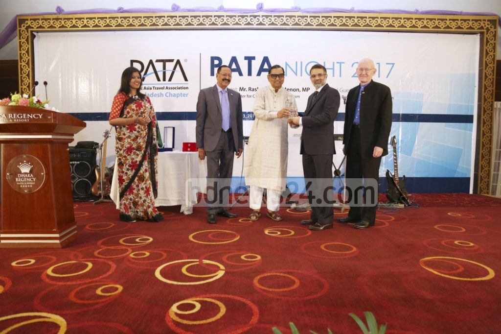 Civil Aviation and Tourism Minister Rashed Khan Menon hands a trophy to bdnews24.com's Editor-in-Chief Toufique Imrose Khalidi at an awards ceremony at Dhaka Regency hotel on Saturday. The Pacific Asia Travel Association or PATA awardedbdnews24.com as the News Media of the Year.