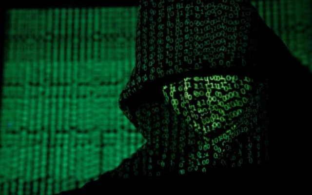 A projection of cyber code on a hooded man is pictured in this illustration picture taken on May 13, 2017. Reuters