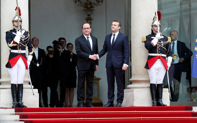 Outgoing French President Francois Hollande greets President-elect Emmanuel Macron who arrives to attend the handover ceremony at the Elysee Palace in Paris, France, May 14, 2017. Reuters