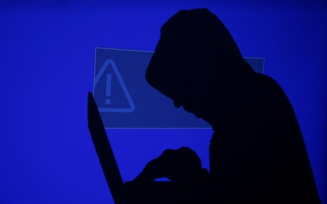 A hooded man holds a laptop computer as blue screen with an exclamation mark is projected on him in this illustration picture taken on May 13, 2017. Reuters
