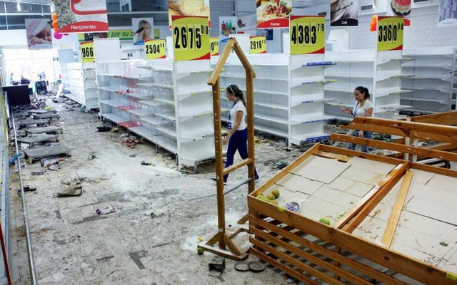 Workers walk next to empty shelves in a supermarket after it was looted in San Cristobal, Venezuela May 17, 2017. Reuters