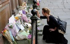 A woman lays flowers for the victims of the Manchester Arena attack, in central Manchester, Britain May 23, 2017. Reuters