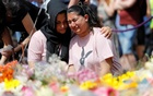 People react as they look at floral tributes for the victims of the Manchester Arena attack, in St Ann's Square, in central Manchester, Britain May 25, 2017. Reuters