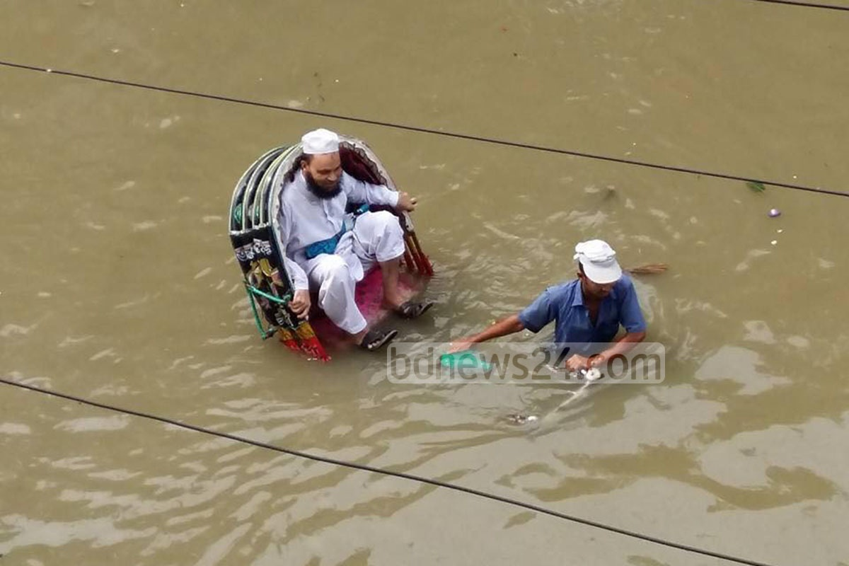 A man sits precariously on a rickshaw in the port city of Chittagong, as the driver slogs through water on Wednesday. Photo: suman babu