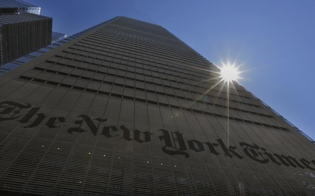 The sun peaks over the New York Times Building in New York. REUTERS