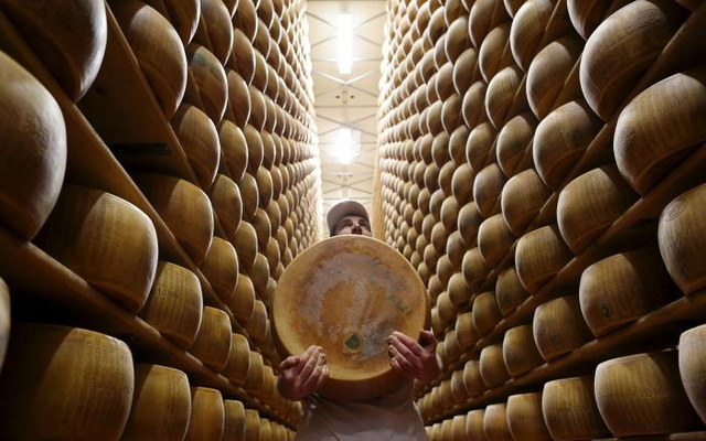 Worker carries fresh Parmesan wheel off storehouse shelf at 4 Madonne Caseificio dell'Emilia dairy cooperative in Modena, Italy, Feb 16, 2016. Reuters