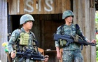 Soldiers stand guard along the main street of Mapandi village as government troops continue their assault on insurgents from the Maute group, who have taken over large parts of Marawi City, Philippines Jun 2, 2017. Reuters