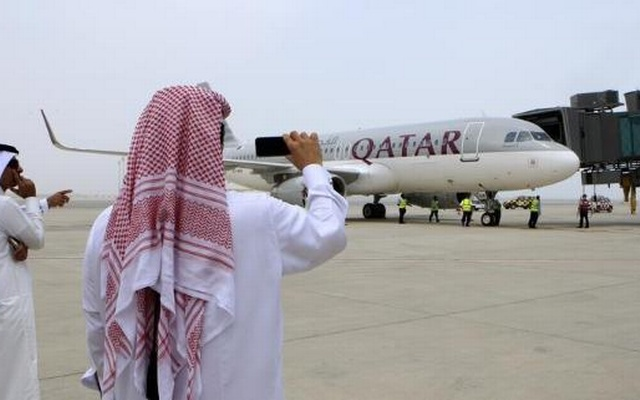 Qatari men take pictures after the Airbus A320-200 aircraft chartered by Qatar Airways landed at Doha's new Hamad International Airport on April 30, 2014. Reuters