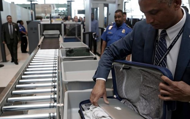 A TSA official removes a laptop from a bag for scanning using the Transport Security Administration's new Automated Screening Lane technology at Terminal 4 of JFK airport in New York City, US, May 17, 2017. Reuters