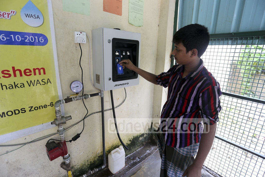 One customer fills up a water jar from the 'Water ATM booth' which works only with a pre-paid card. Dhaka WASA installed its first booth in Fakirapool as part of its austerity measures. Photo: asif mahmud ove