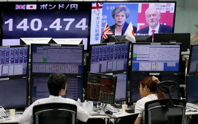 Employees of a foreign exchange trading company work near monitors showing TV news on Britain's general election and the Japanese yen's exchange rate against the British pound in Tokyo, Japan June 9, 2017. Reuters