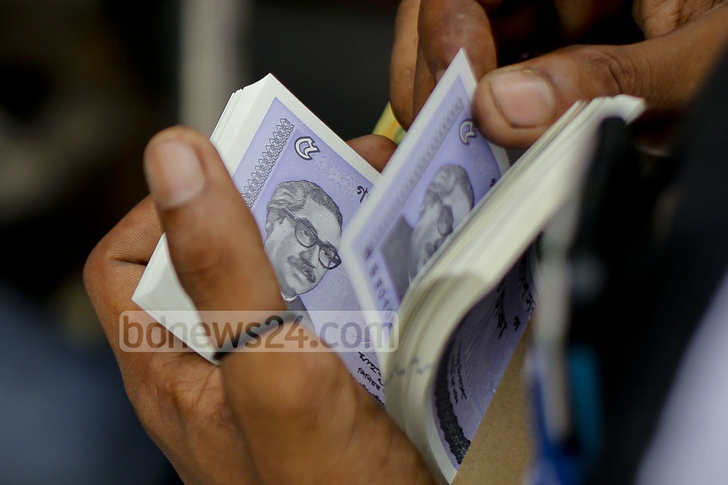 A buyer counts new notes in front of a stall in Dhaka's Gulistan. Photo: asaduzzaman pramanik