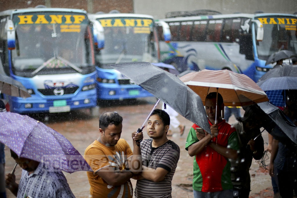 Customers wait in the rain on Monday to buy early bus tickets for Eid trips home. Photo: asaduzzaman pramanik