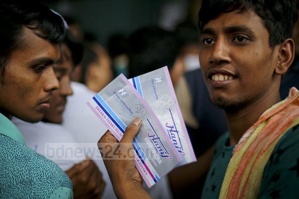 A customer smiles after getting bus tickets for Eid trips home. Photo taken on Monday at a bus counter in Dhaka's Gabtoli. Photo: asaduzzaman pramanik