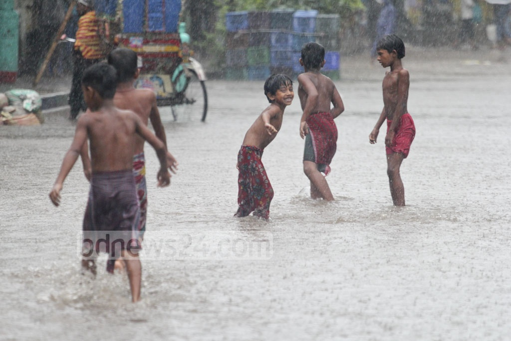 Children play in a street flooded by the rain on Monday. Photo: asif mahmud ove