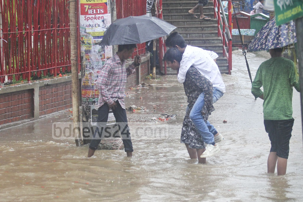 A man climbs on the back of another person to cross a flooded street at Dhaka's Mirpur on Monday. Photo: asif mahmud ove