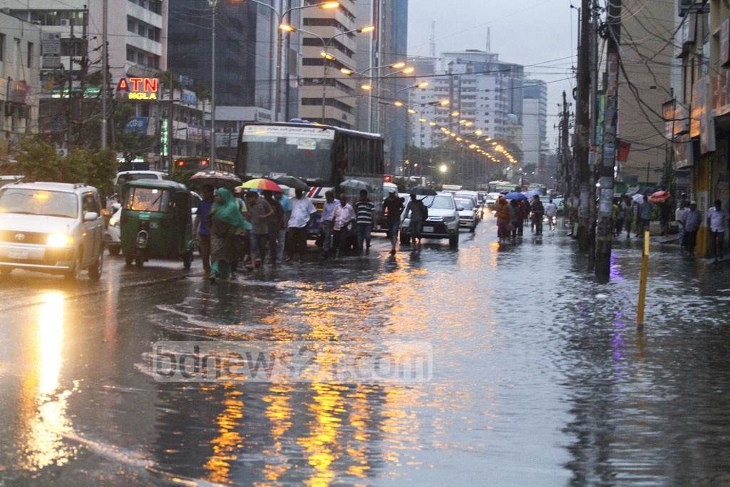 The footpath has gone underwater so people queue up where the Kazi Nazrul Islam Avenue was still visible after continuous rains on Monday. Photo: abdul mannan