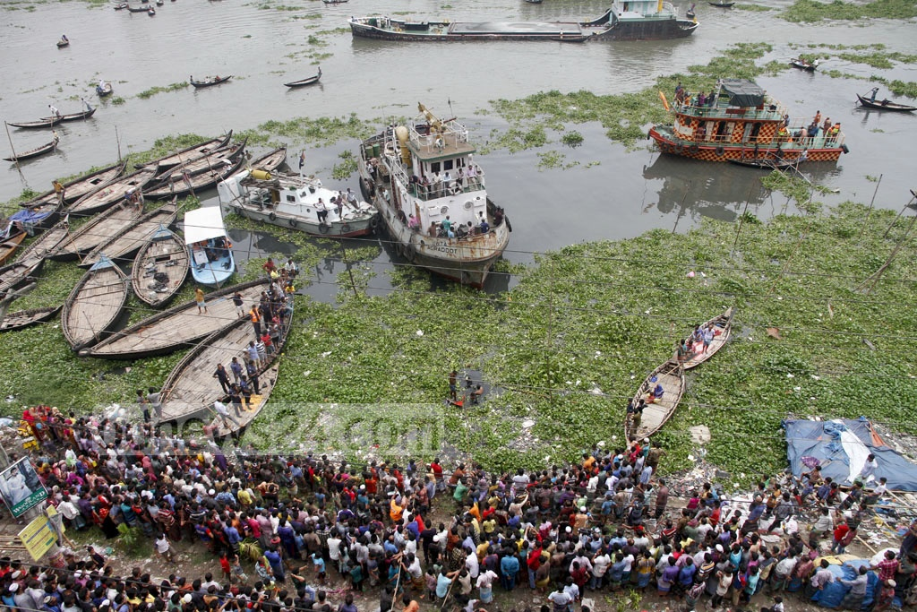Onlookers crowd the bank of Buriganga River at Dhaka's Keraniganj as divers try locate a trawler that capsized in the river on Tuesday with around 60 people on it. Photo: tanvir ahammed