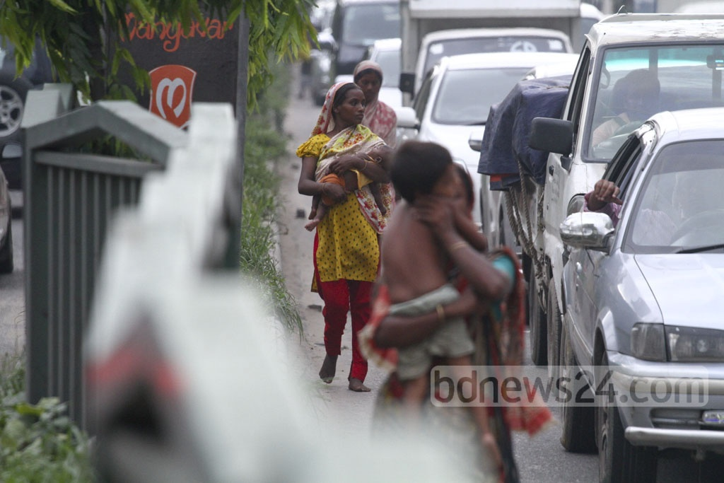 Women and children trying for as much alms as possible from passengers caught up at traffic signals. The photo was taken at Manik Mia Avenue of the capital on Wednesday. Photo: abdul mannan