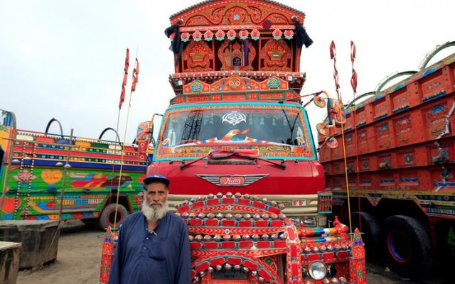 A security guard poses for a portrait in front of his favourite decorated truck at a truck stop outside Faisalabad, Pakistan, May 3, 2017. Reuters