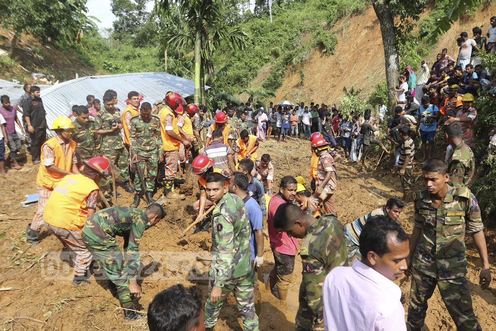 Rescuers from Fire Service, army and local people work in Rangamati's Muslimpara to pull out people from mud on Wednesday as landslides kill scores in the hill districts.