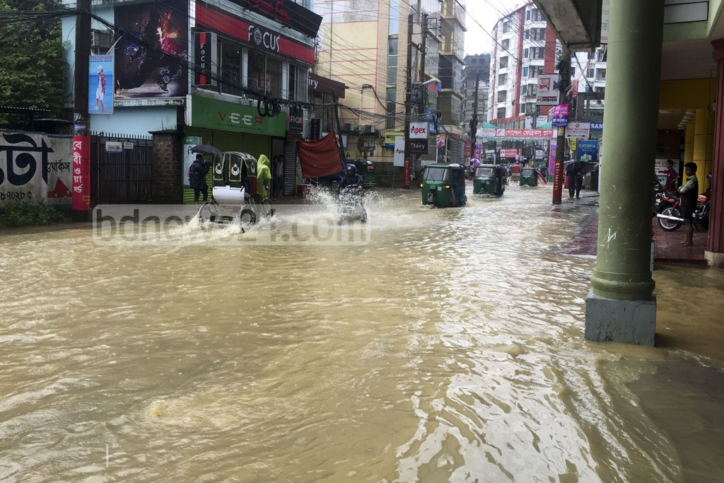People struggle to pass a street in Sylhet city that went underwater as heavy rains continued on Wednesday.