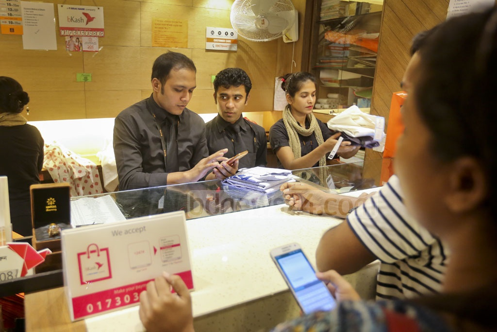 An Aarong salesman is receiving payment through bKash at the fashion brand's Science Laboratory outlet. Photo: asaduzzaman pramanik
