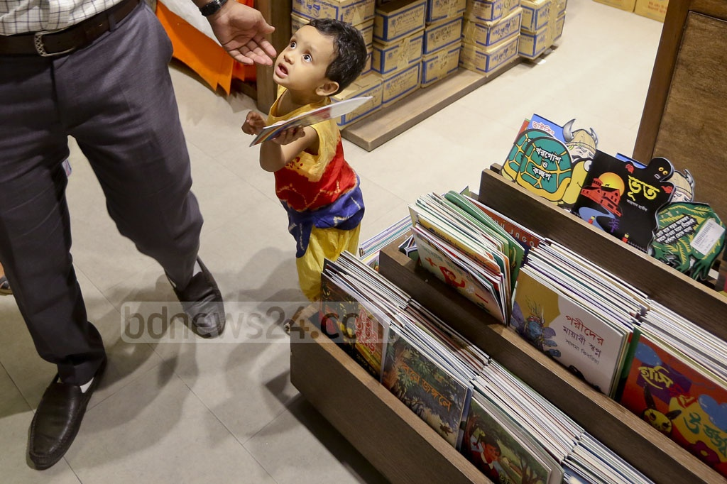 A child gestures with a book during Eid shopping at Aarong's Science Laboratory outlet. Photo: asaduzzaman pramanik