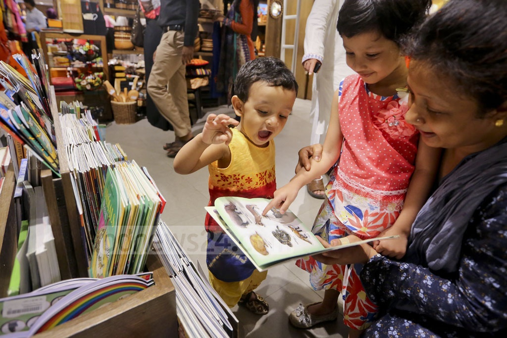 Children leaf through books during Eid shopping at Aarong's Science Laboratory outlet. Photo: asaduzzaman pramanik