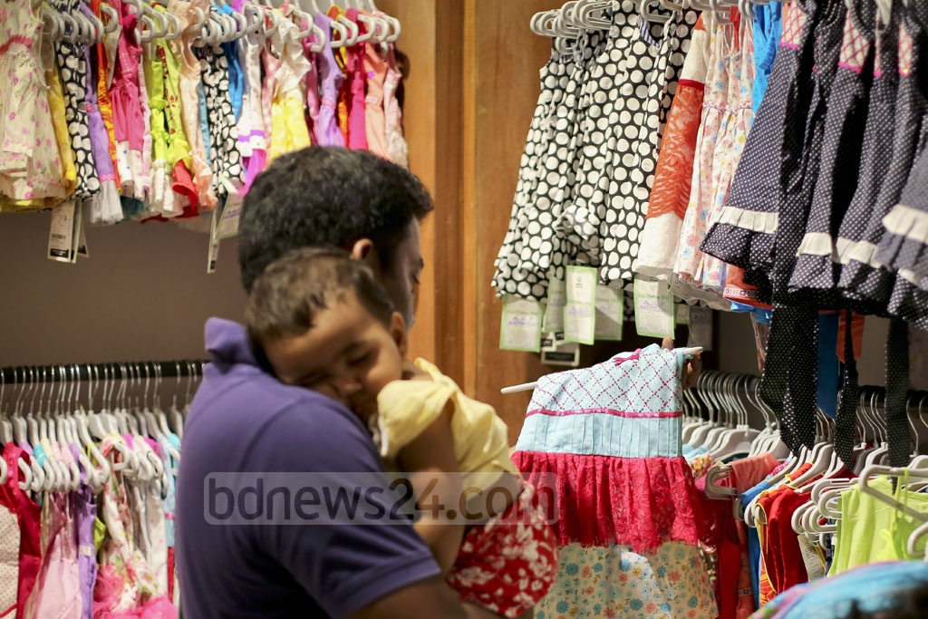 A man carrying a child looks at baby clothing items. Photo: asaduzzaman pramanik