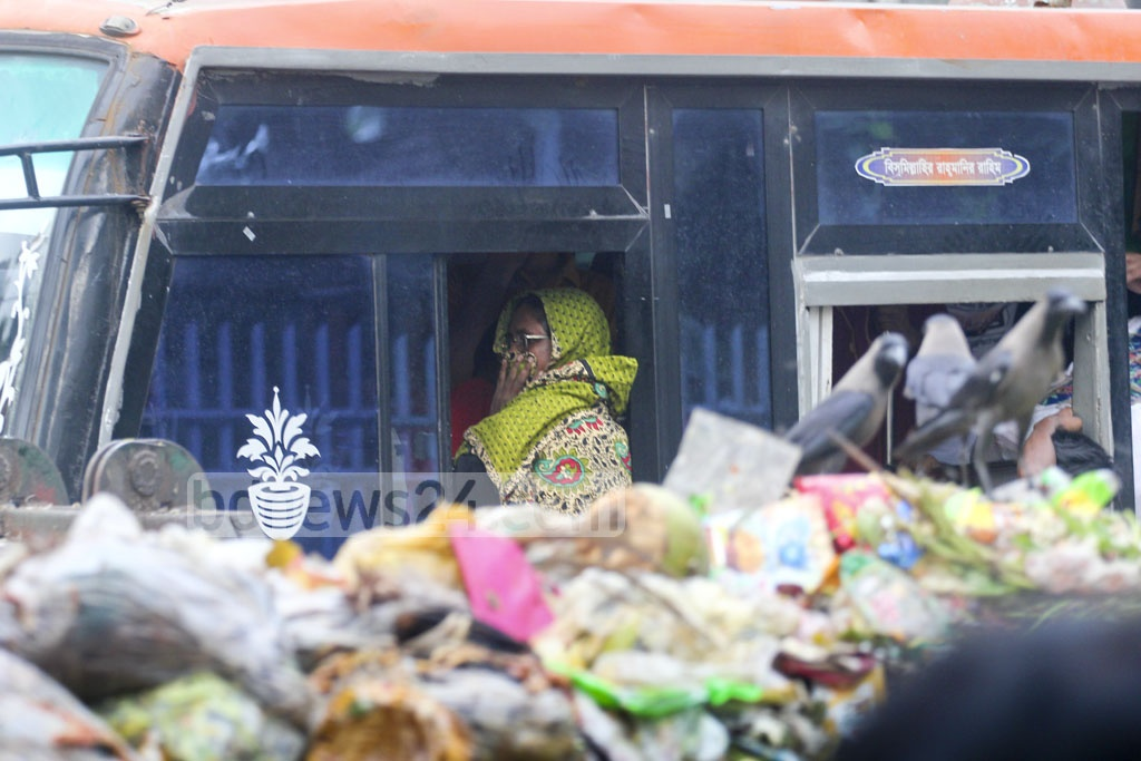 A bus passenger tries to ward off the smell of rotting waste spewing out of a roadside dumpster near Kalagabagn on Friday. Photo: asif mahmud ove