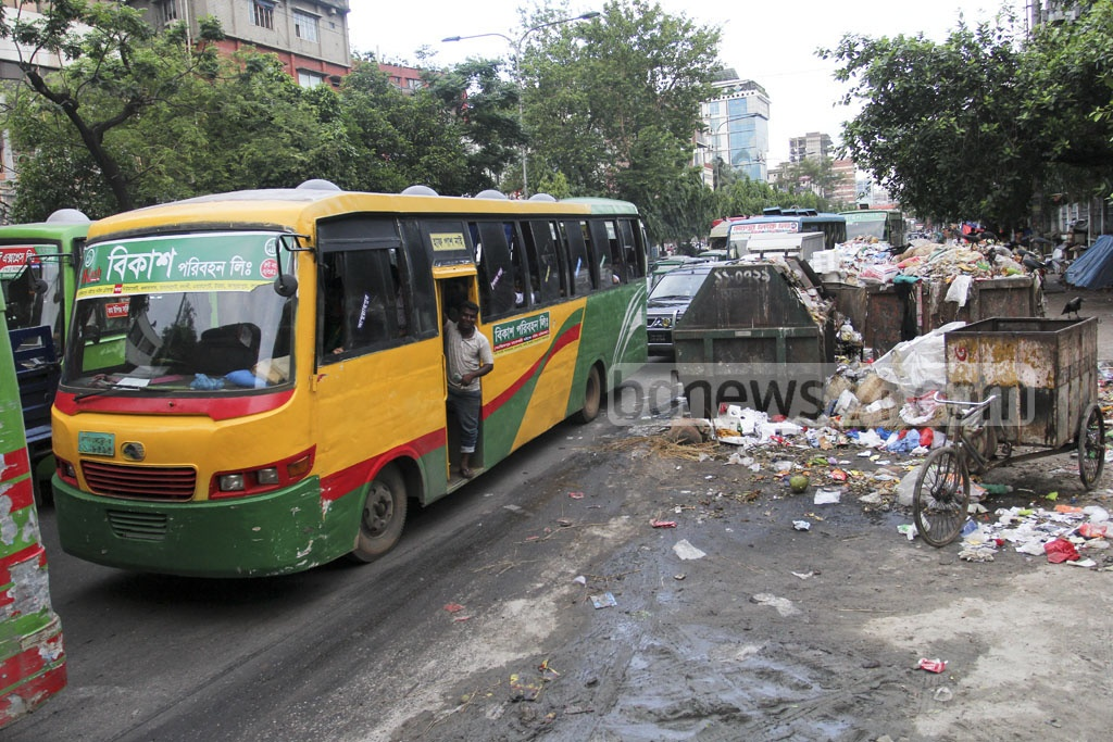 Dhaka forces its citizens to bear the sight and smell of waste spewing out of dustbins. Photos of commuters covering their noses were taken from Mirpur road on Friday. Photo: asif mahmud ove