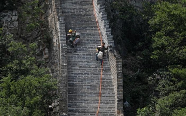 Workers carry their tools and belongings as they climb down the Jiankou section of the Great Wall, located in Huairou District, north of Beijing, China, Jun 7, 2017. Reuters