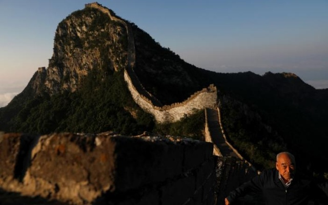 Cheng Yongmao, the engineer in charge of the reconstruction project on the Jiankou section of the Great Wall, looks as the sun rises over the wall, located in Huairou District, north of Beijing, China, Jun 7, 2017. Reuters