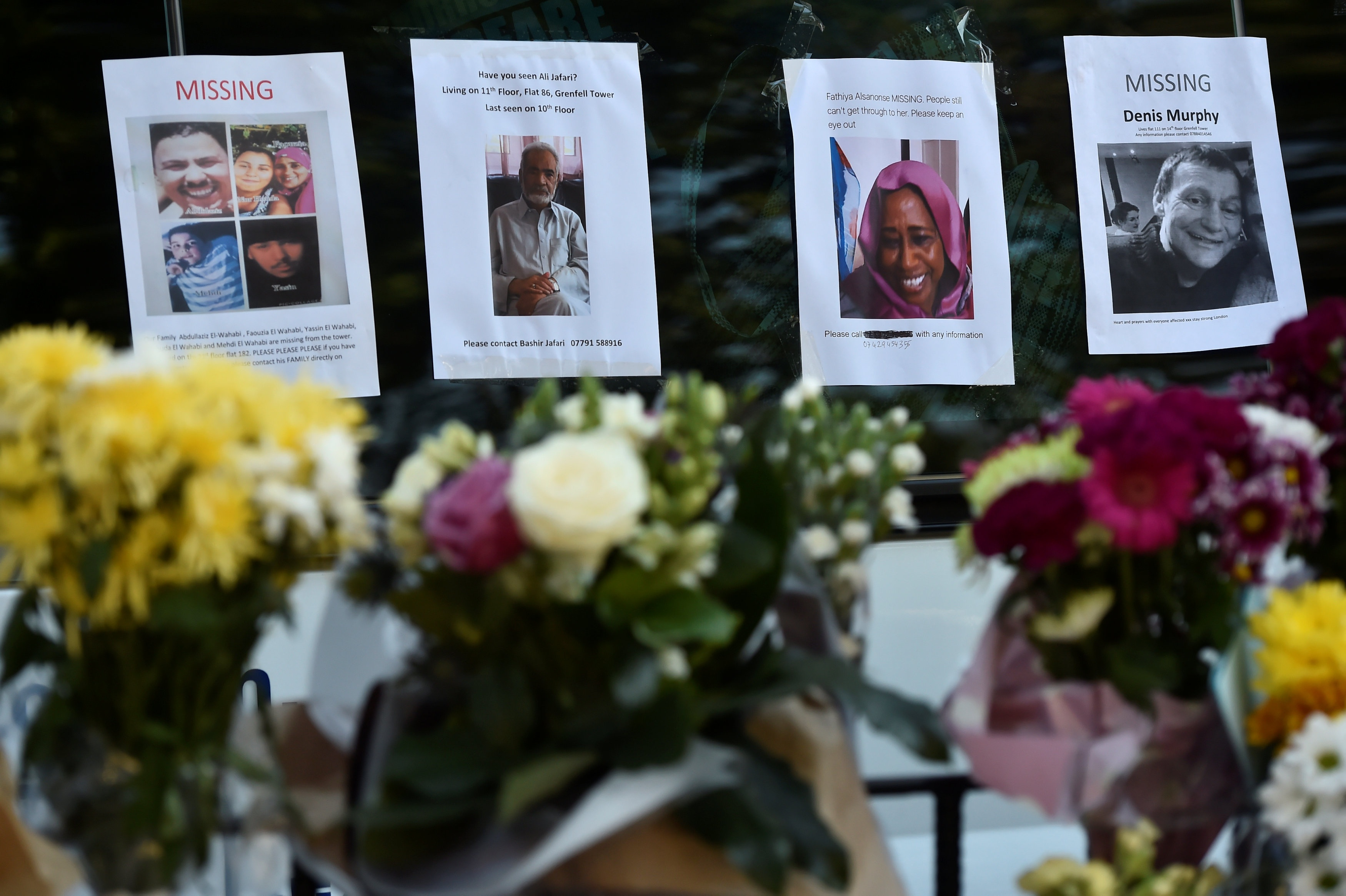 Homemade posters appealing for information on people missing since the Grenfell apartment tower block caught fire are seen behind flowers in London on June 17. Reuters