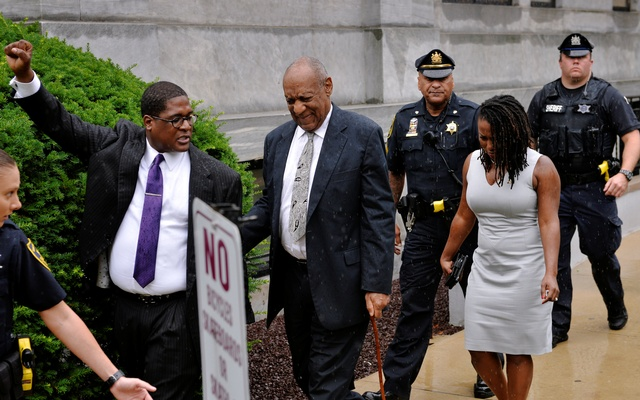 Actor and comedian Bill Cosby walks as his publicist, Andrew Wyatt, raises his fist after a judge declared a mistrial in his sexual assault trial at the Montgomery County Courthouse in Pennsylvania, US, on June 17.