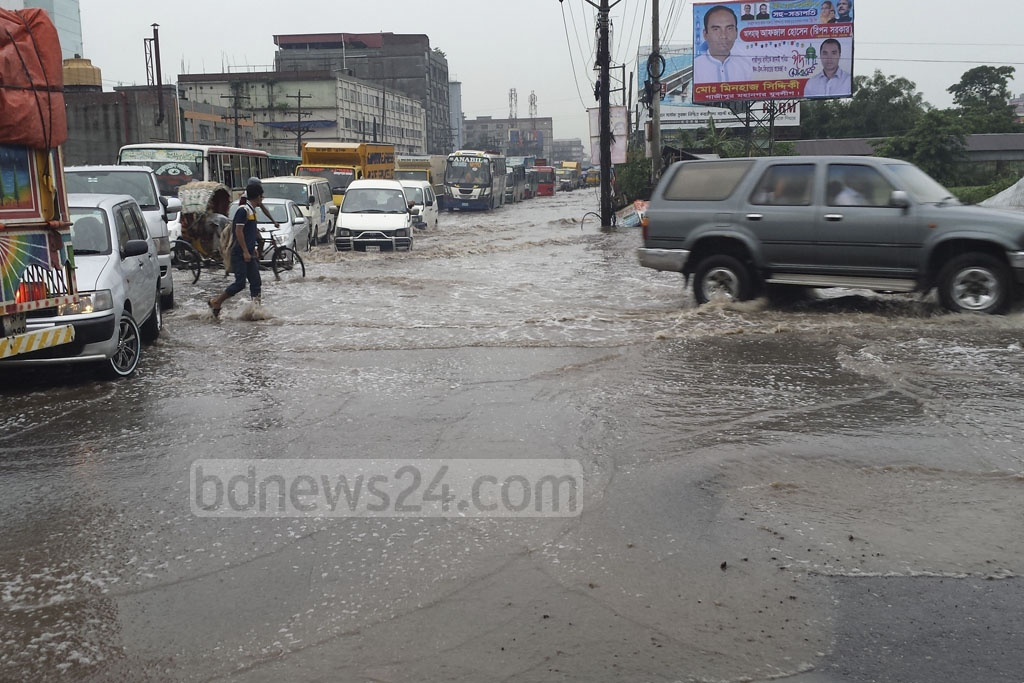 Cars struggle to pass through a section of the Dhaka-Mymensingh Highway that was flooded after heavy rains on Monday.