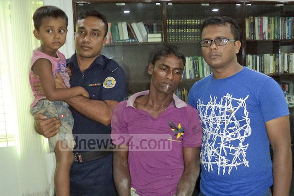 A kidnapper is photographed at a police station on Monday, next to his five-year-old victim and detectives who found him, a day after the abduction in Brahmanbaria.