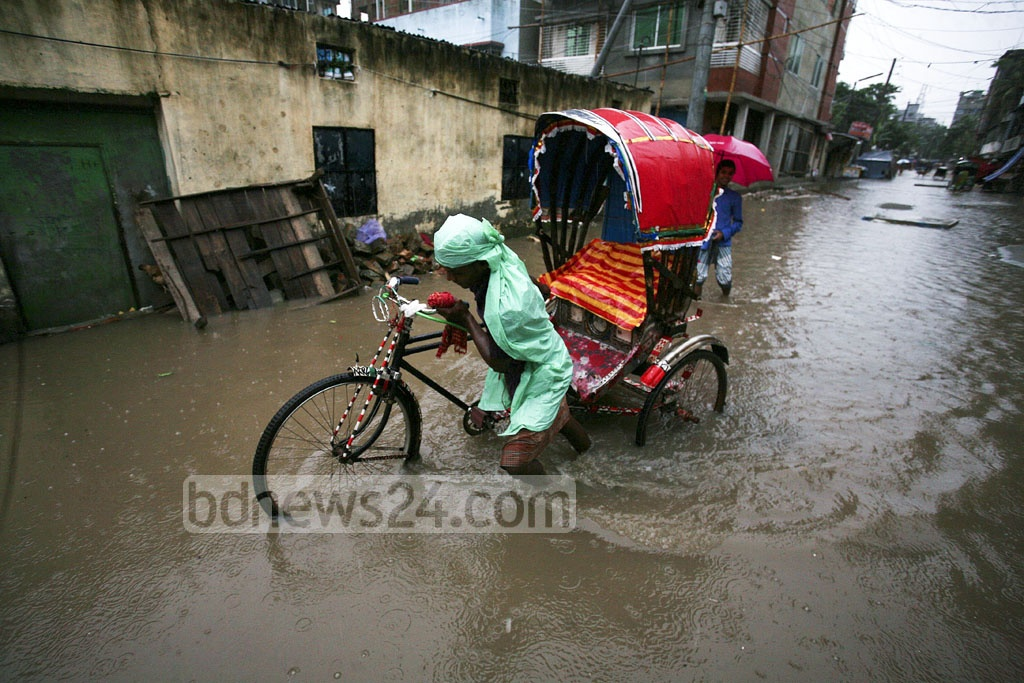 A rickshaw-puller struggles to make his way through the knee-deep water clogged on this lane at Dhaka's Pallabi neighbourhood on Monday.